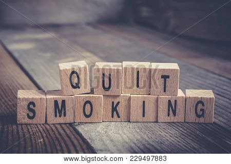 Closeup Of The Words Quit Smoking Formed By Wooden Blocks On A Wooden Floor