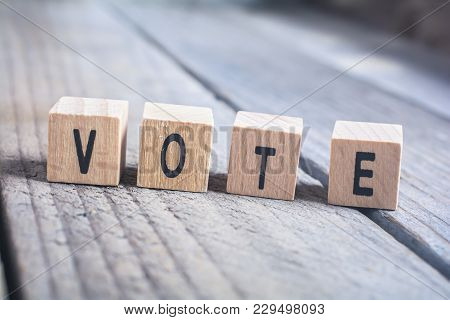 Macro Of The Word Vote Formed By Wooden Blocks On A Wooden Floor