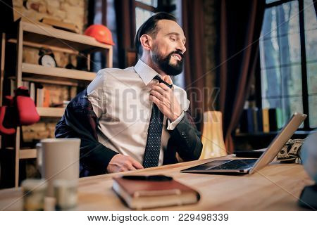 Businessman Having Relaxing Talk On Skype With Friend, .untie His Shirt.