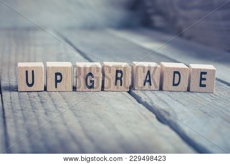 Closeup Of The Word Upgrade Formed By Wooden Blocks On A Wooden Floor