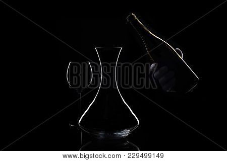 Glass, Bottle And Preparation For Decanting Red Wine. Hand In White Glove Holds Bottle Of Wine And D