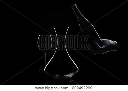 Silhouettes Of Wine Glass, Bottle And Decanter At Isolated Black. Hand In White Glove Holds Bottle O