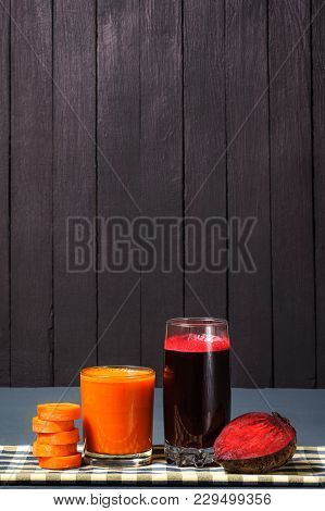 Natural Juices From Carrots And Beets. The Juice Is Poured Into A Clear Glass, Which Stands On A Tab