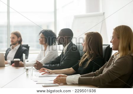 Diverse Smiling Business People Sitting At Conference Table At Group Meeting Or Corporate Briefing,