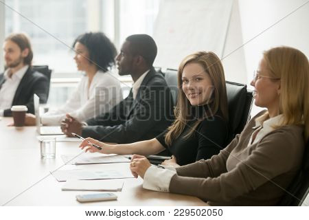 Young Smiling Businesswoman Looking At Camera At Corporate Group Meeting, Business Training Particip