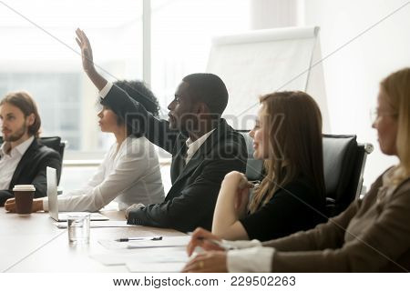 African American Businessman Raising Hand At Diverse Team Meeting, Black Training Participant Listen