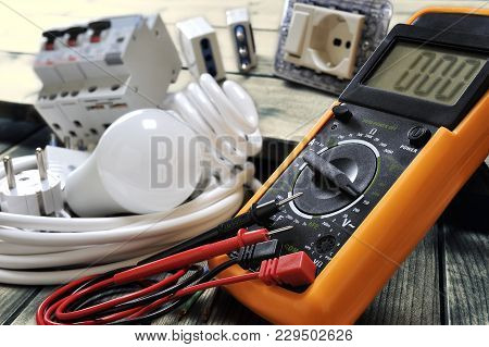 Close-up Of A Tester And Other Components For Residential Electrical Installation On Rustic Wooden T