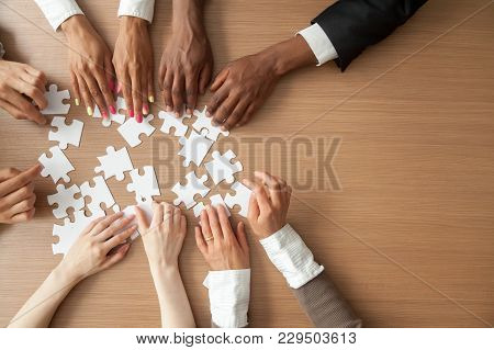 Hands Of Multi-ethnic Team Assembling Jigsaw Puzzle, Multiracial Group Of Black And White People Joi