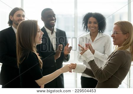 Funny Smiling Businesswomen Holding Hands Celebrating Success While Diverse Team Applauding, Female