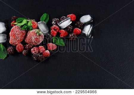 Frozen Raspberry, Blackberry, Strawberries Mint Leaves, Pieces Of Ice On A Black Shale Board, Frozen