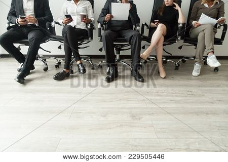 Diverse Business People Waiting In Queue Holding Smartphones And Resumes, Multiracial Men And Women