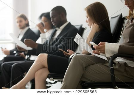 Multi-ethnic Applicants Sitting In Queue Preparing For Interview, Black And White Vacancy Candidates