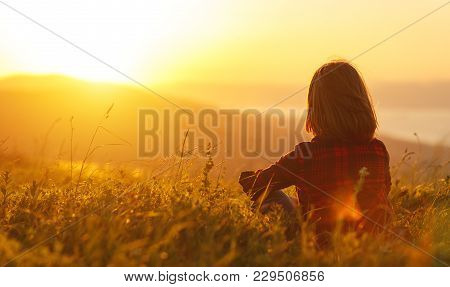Woman Sits With Her Back In The Field And Admires The Sunset In The Mountains