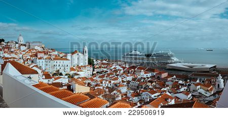 Panoramic Shot Of Rooftin The Oldest District Alfama In Lisbon. Cruise Boat On The Tagus River. Lisb