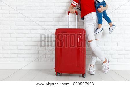 Concept Travel And Tourism With Child. Legs Of Mother And Child   With Suitcase Near Empty Wall