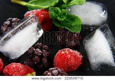Macro Frozen Raspberry, Blackberry, Strawberries Mint Leaves, Pieces Of Ice On A Black Shale Board,