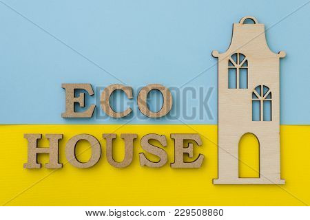 The Concept Of Eco Housing. Word Eco House, With Yellow Blue Background, Wooden Model Of The House.