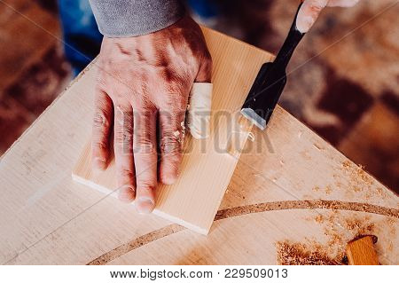 Carpenter Use A Chisel To Shapes A Wooden Plank. Toned Image.