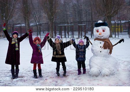 A Small Cheerful Girls Near Big Funny Snowman. A Cute Little Sisters Has Fun In Winter Park, Wintert