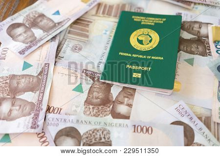 Nigerian Passport With Nigerian Naira Banknotes Spread Out Below