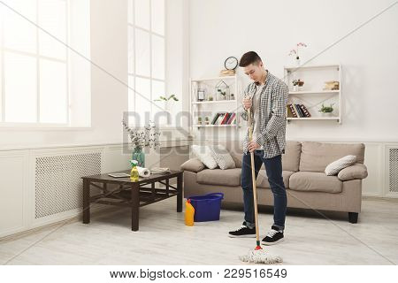 Young Man Cleaning Home With Mop And Detergents. Housekeeping, Spring-cleaning And Tidying Up Concep