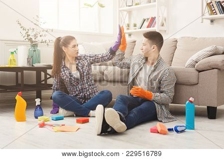 Housewife And Her Husband Giving High Five After Cleaning Home With Sponges, Brushes And Detergents.