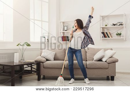 Happy Woman Cleaning Home, Singing At Mop Like At Microphone And Having Fun, Copy Space. Housework,