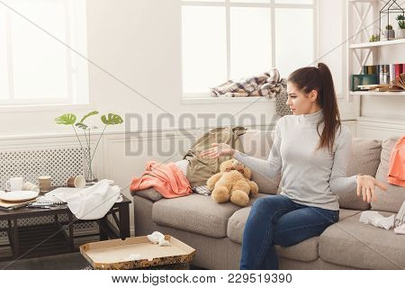 Desperate helpless woman sitting on sofa in messy living room. Young girl surrounded by many stack of clothes. Disorder and mess at home, copy space poster