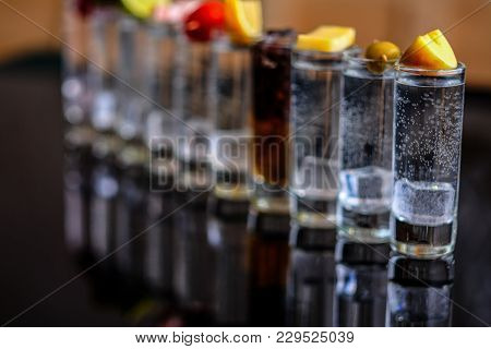 A Shots Of Alcohol Are Reflected On The Surface. Over Every Shot Something Lies-lime, Tomatoes, Oliv