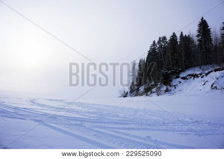Winter Road (frozen River With A Highly Wooded Shore) With Traces Of Snowmobiles, With A Horizon, Lo