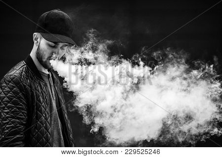 Vape Man. Portrait Of A Handsome Young White Guy In A Modern Black Cap Vaping And Letting Off Puffs