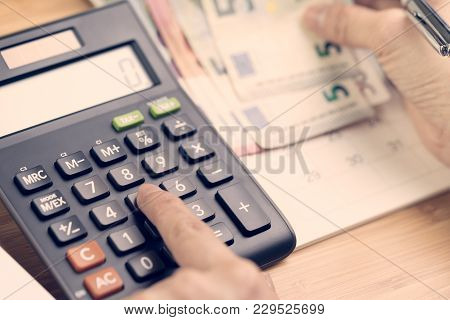 Cost Calculation, Payment Day Concept, Hand Put Finger On Calculator And Other Hand Holding Pen And