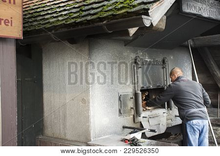 German Old Men Use Firewood Stove Old Style Cooking Bread At Restaurantin Black Forest Or Schwarzwal