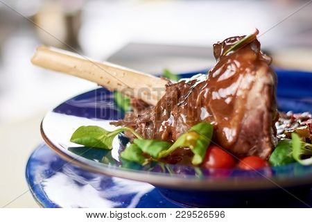 Braised Lamb Shank With Vegetable Ratatouille. Slow Cooked Lamb Shank In Restaurant Close Up. Roaste
