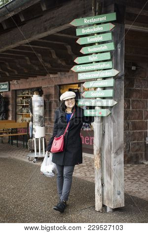 Asian Thai Woman Travel And Posing With Information Guide Board At Souvenir Gift Shop In Black Fores