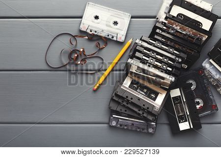 Retro Audio Cassettes And Pencil On Gray Wooden Planks Background. Top View On Vintage Tapes And Sim