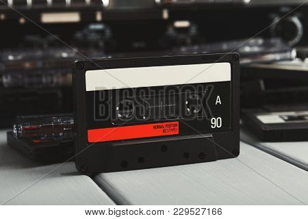Retro Audio Cassette In Front Of Vintage Tape Recorder And Heap Of Tapes On Gray Background. Side Vi