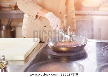 Chef Frying Meat With Garlic. Hands Of Male Chef Frying Duck Breast At Professional Kitchen. Man At