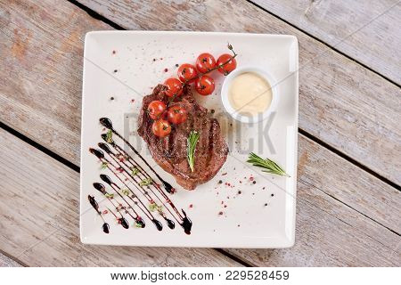 Steak Ribeye With Tomatoes And Rosemary. Steak Ribeye Served With Cherry Tomatoes And Rosemary, Top