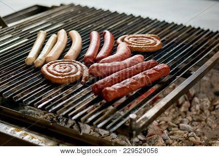 Assorted Sausages Grilling Over Coals On Barbecue. Assortment Of Different Sausages Grilling On Iron