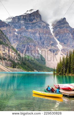 Lake Louise, Canada - August 22, 2014: Moraine Lake On A Cloudy Day With Some Visitors Preparing To