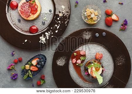 Exquisite Restaurant Desserts. Chocolate And Vanilla Souffle And Lemon Cheesecake With Berry Spheres