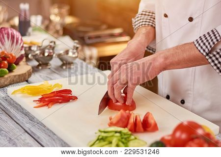 Chef Slicing Tomato On Cutting Board. Male Chef Hands Cutting Fresh Vegetables For Salad. Chef At Wo