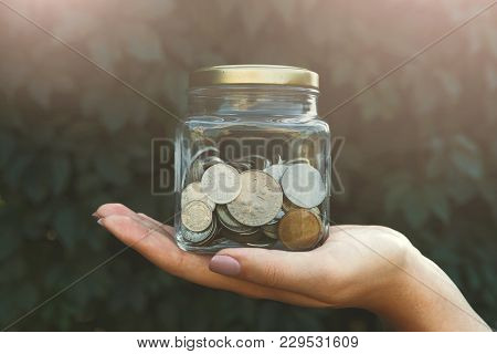Hand Holding Glass Jar With Coins With Save Label On Green Leaves Background. Money Saving For House