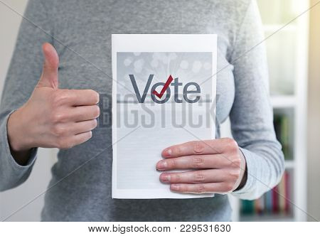 Hand Of A Person Holding Vote Sign With Thumbs Up Expression