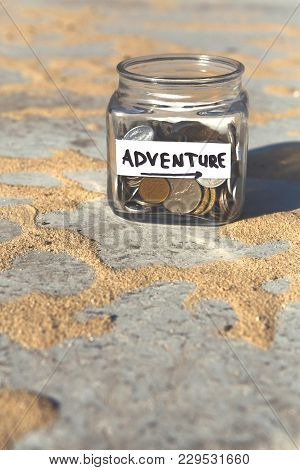 Glass Jar With Coins For Adventure On Gray Floor With Sand Background, Copy Space. Money Box, Distri