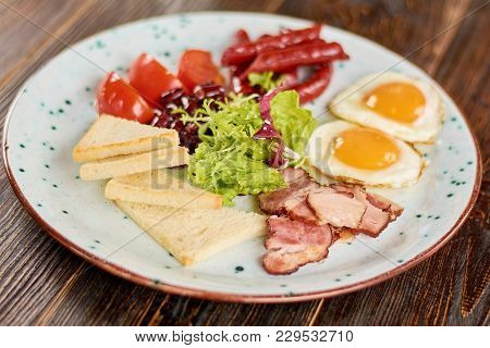 English Breakfast Served With Green Salad. English Breakfast With Fried Eggs, Baked Sausages And Bac