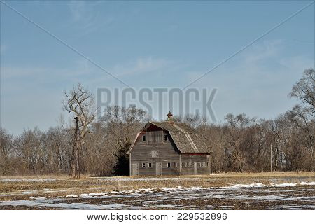 An Abandoned Barn And Old Windmill On A Abandoned Farmstead.
