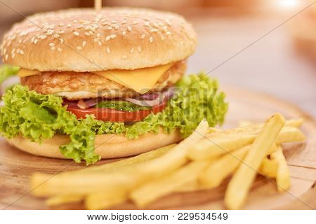 Close Up Of Hamburger And French Fries. Delicious Burger With Fresh Chicken And Vegetables. Still Li