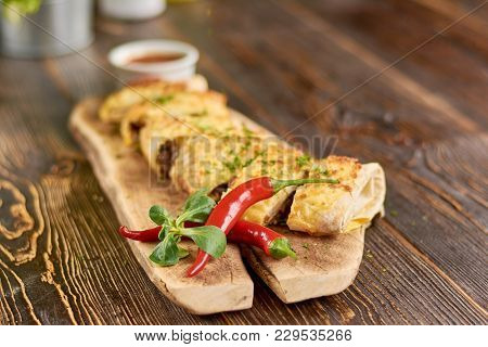 Mexican Burrito Served With Chili Pepper. Appetizing Mexican Burrito Decorated With Fresh Basil And